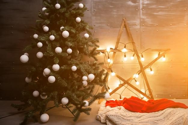 Weihnachtsbaum mit lichtern und stern in einem dachbodenraum