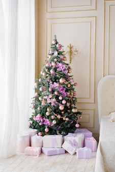 Weihnachtsbaum mit lila spielwaren und geschenken darunter