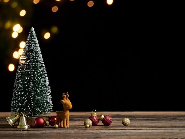 Weihnachtsbaum mit rentier auf rustikalem weinlese-holztisch. bokeh-effekt, platz für text