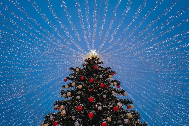 Weihnachtsbaum mit rotem spielzeugkugelstern und goldenen lichtern in der festlichen abendstadt-bokeh-girlande