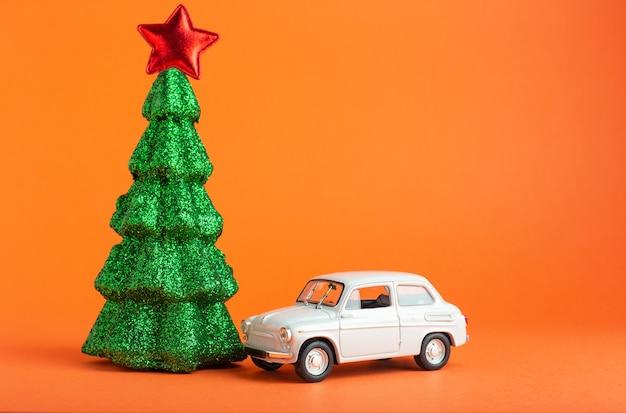 Weihnachtsbaum mit rotem stern oben in der nähe von weißem autospielzeug. kreativer miniaturweihnachtsbaum und -auto auf orangefarbenem hintergrund. geschenklieferungskonzept.