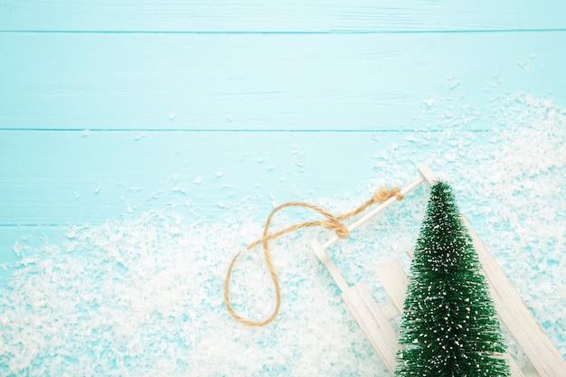 Weihnachtsbaum mit schlitten auf blauem hölzernem hintergrund
