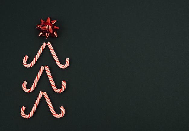 Weihnachtsbaum mit stern gemacht mit zuckerstangen auf einem schwarzen hintergrund. weihnachtskonzept.