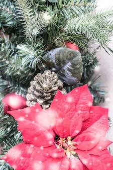 Weihnachtsbaum mit tannenzapfen und einer roten blume