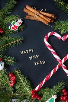 Weihnachtsbaum mit verzierungen und süßigkeit auf einem schwarzen hintergrund. die inschrift frohes neues jahr