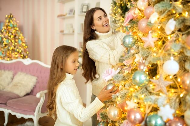 Weihnachtsbaum mutter und tochter schmücken gemeinsam den weihnachtsbaum und sehen zufrieden aus