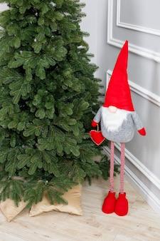 Weihnachtsbaum-nahaufnahme ohne spielzeug. roter spielzeugelfengnom nahe dem weihnachtsbaum. gute neujahrsstimmung.