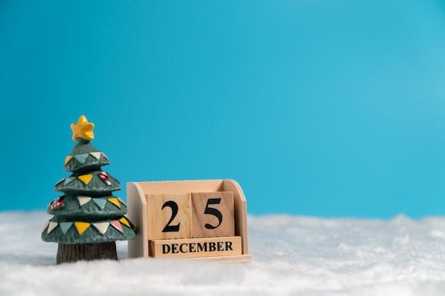 Weihnachtsbaum neben holzblockkalender stellte am weihnachtsdatum am 25. dezember auf weiß ein