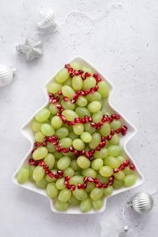 Weihnachtsbaum obstsalat mit trauben und granatapfel