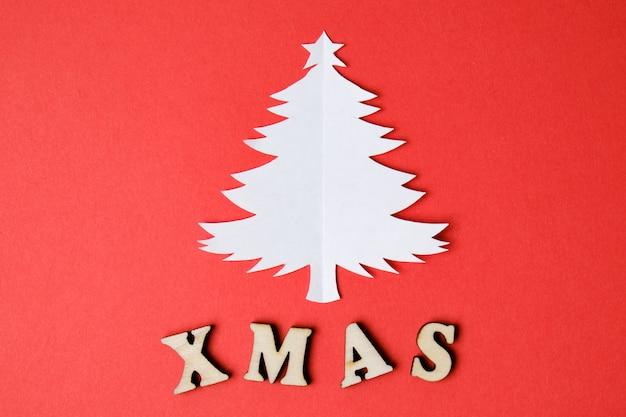 Weihnachtsbaum schnitt vom papier mit aufschrift weihnachten in den hölzernen buchstaben