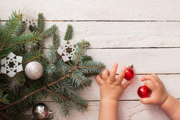 Weihnachtsbaum und babyhände auf weißem hintergrund aus holz. weiße schneeflocken. flache lage, ansicht von oben. platz kopieren