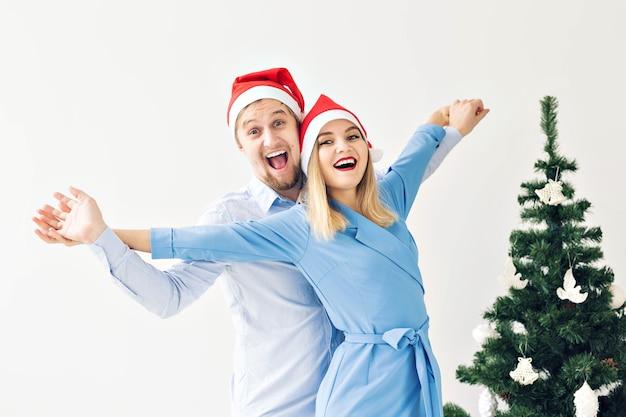 Weihnachtsbaum und feiertagskonzept - glückliche lächelnde familie, die weihnachtsmützen trägt, die zu hause feiern.