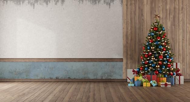 Weihnachtsbaum und geschenk gegen holztafel im alten leeren raum