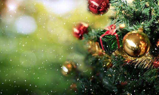 Weihnachtsbaum und geschenkbox auf grünem bokeh verwischen hintergrund.