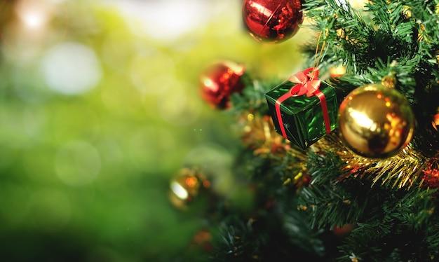 Weihnachtsbaum und geschenkbox auf grüner bokeh-unschärfe.