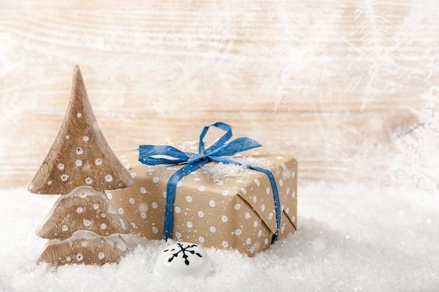 Weihnachtsbaum und geschenkbox auf schnee