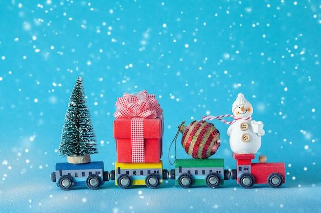 Weihnachtsbaum und geschenkbox, ball und schneemann auf spielzeugeisenbahn auf blau