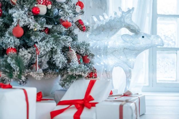 Weihnachtsbaum und geschenkboxen im innenraum mit rotwild. weihnachtsbaum mit spielzeug geschmückt, viele geschenke mit rotem band um den weihnachtsbaum gebunden. neues jahr weihnachtsinterieur