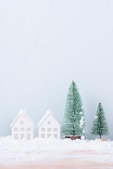 Weihnachtsbaum und haus mit schneefrostfeld des natürlichen landschaftshintergrundes für feier und frohes neues jahr.