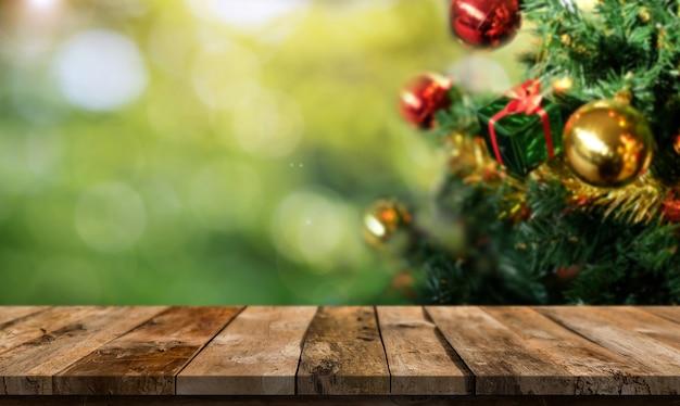 Weihnachtsbaum und holztisch mit freiem platz auf grüner bokeh-unschärfe.