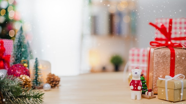 Weihnachtsbaum und neujahrsfeiertagsgeschenkbox mit dekorativer verzierung auf holztisch mit schneefall. geschenke und glückwünsche banner hintergrundkonzept.