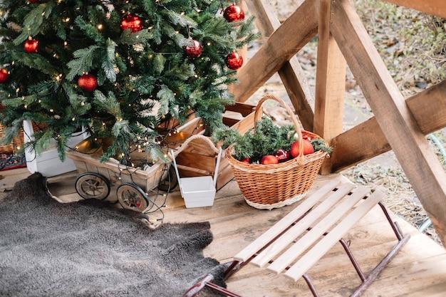 Weihnachtsbaum und schlitten auf der veranda eines holzhauses.