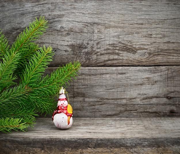 Weihnachtsbaum und schneemannspielzeug auf hölzernem hintergrund