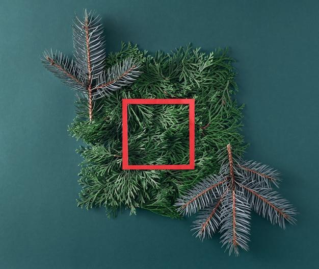 Weihnachtsbaum- und thujazweige mit rotem papierrahmen auf grünem hintergrund. neujahrskonzept.