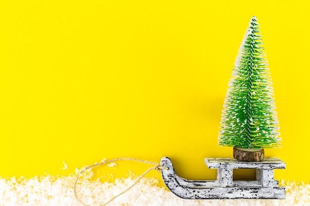Weihnachtsbaum und vintage holzschlitten über trendigen hintergrund mit schnee. grußkarte der frohen weihnachten und des guten rutsch ins neue jahr. minimaler winterhintergrund. flache kopienraum