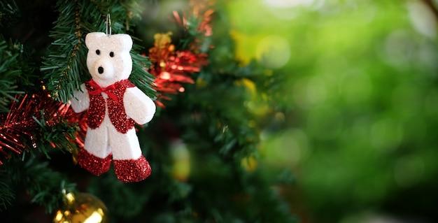 Weihnachtsbaum und weißer teddybär auf grünem bokeh verwischen hintergrund.