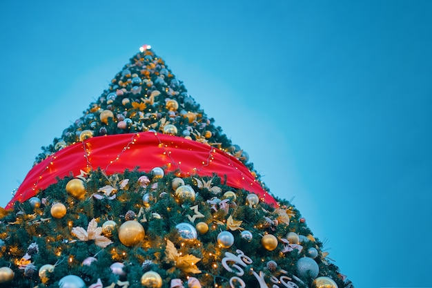 Weihnachtsbaum unter blauem himmel. unteransicht des festlich geschmückten baumes. neujahr winterferien