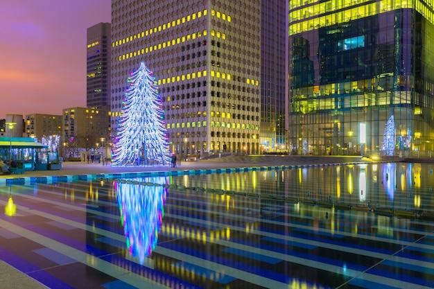 Weihnachtsbaum unter den wolkenkratzern in paris, frankreich