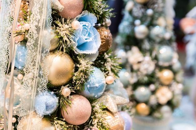Weihnachtsbaum verziert mit blauen und goldenen kugeln nahaufnahme. weihnachtsdekor, neues jahr. winterferienfeier