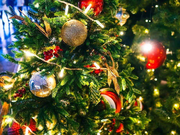 Weihnachtsbaum verziert mit einer girlande und weihnachtsspielzeug. nahaufnahme