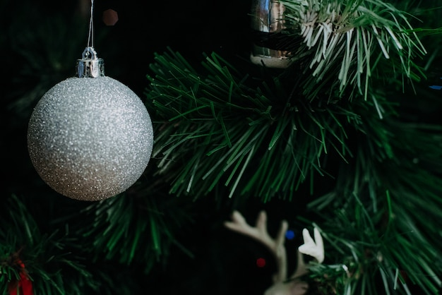 Weihnachtsbaum verziert mit einer girlande und weihnachtsspielzeug. nahaufnahme.