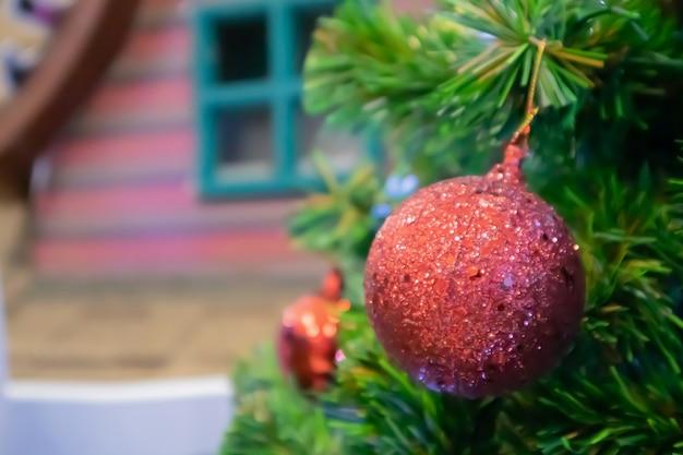 Weihnachtsbaum verziert mit roter kugel auf kiefernzweighintergrund