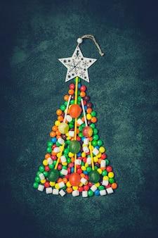 Weihnachtsbaum von mehrfarbenbonbons auf weinlesegrünhintergrund