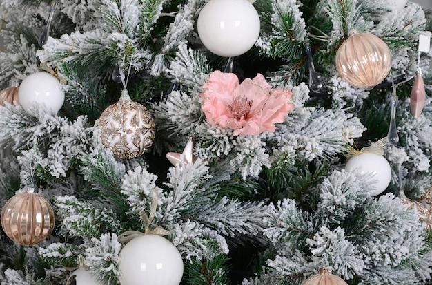 Weihnachtsbaumabschluß oben verzieren. dekorationsbirne, schneebedeckter grüner tannenbaum, rosa weihnachtsspielwaren und lichter