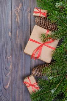Weihnachtsbaumast, dekorationen und geschenkbox auf weißem holztisch