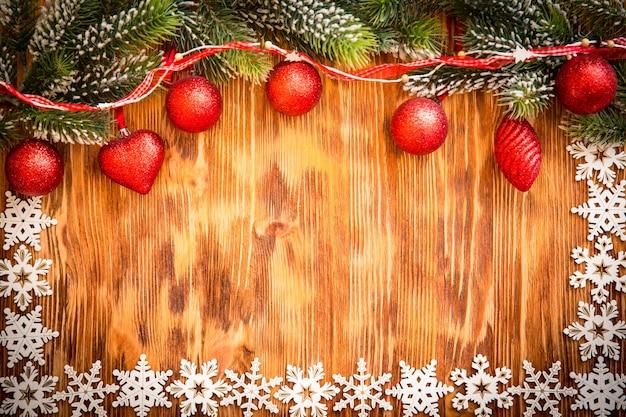 Weihnachtsbaumast mit dekorationen auf holzhintergrund. weihnachtsferienkonzept