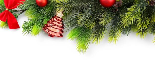 Weihnachtsbaumast mit roten beeren und dekorationen auf weißer oberfläche