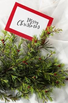 Weihnachtsbaumaste auf weißem stoff mit weihnachtskartenmodell