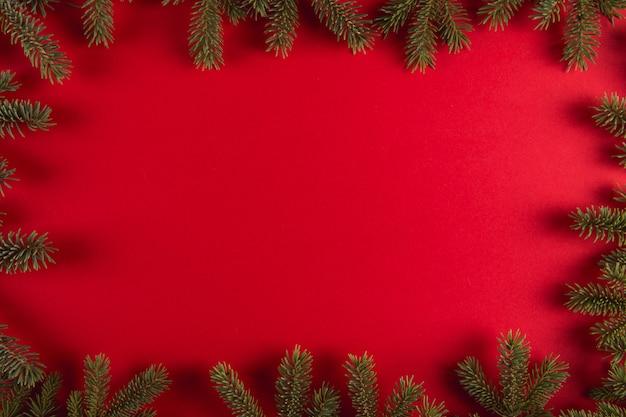 Weihnachtsbaumaste in form eines rahmens auf einem rot, weihnachten, grußkarte copyspace.
