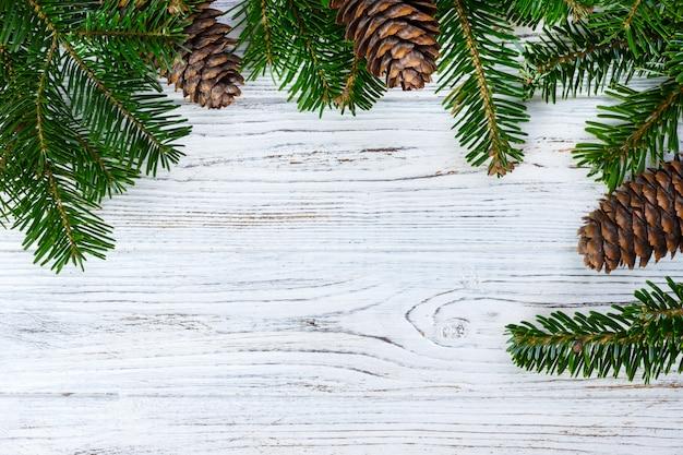Weihnachtsbaumaste mit kegel auf der weißen hölzernen beschaffenheit bereit. winterurlaub hintergrund
