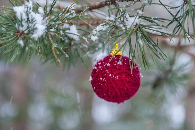 Weihnachtsbaumdekoration gemacht vom roten garnball auf grün