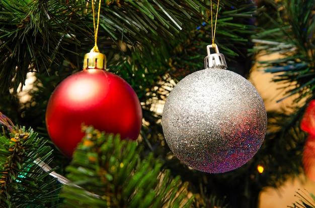 Weihnachtsbaumdekoration. kugeln, sternengirlande auf einem baum. rote bögen auf einem neujahrsbaum. der festliche baum ist mit hellen spielzeugen geschmückt. neujahrsstimmung. frohe weihnachten