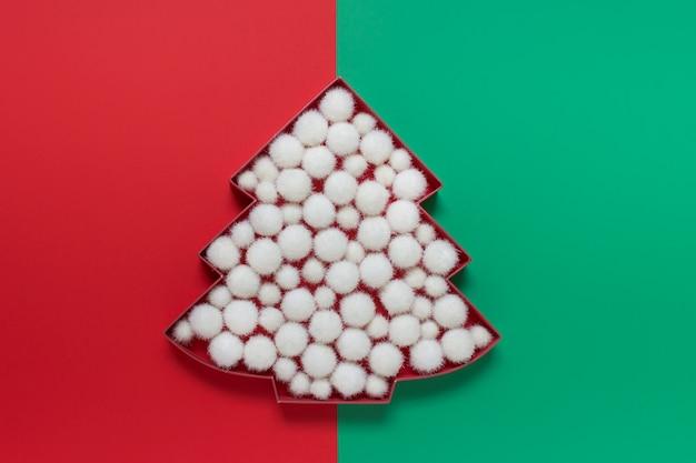 Weihnachtsbaumkarton gefüllt mit weißen flauschigen schneebällen auf doppeltem zweifarbigem rotem und grünem hintergrund.