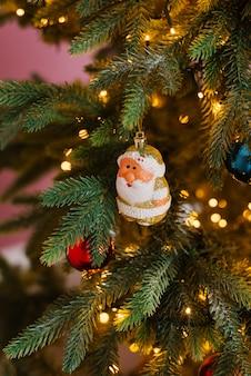 Weihnachtsbaumspielzeug santa claus oder santa claus auf dem weihnachtsbaum mit lichtern