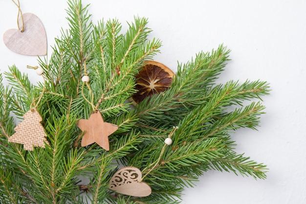 Weihnachtsbaumspielzeug und natürliche fichtenzweige auf einem weißen hintergrund-draufsicht-kopierplatz, hausgemachtes umweltfreundliches weihnachtsbaumspielzeug auf frischen fichtenzweigen