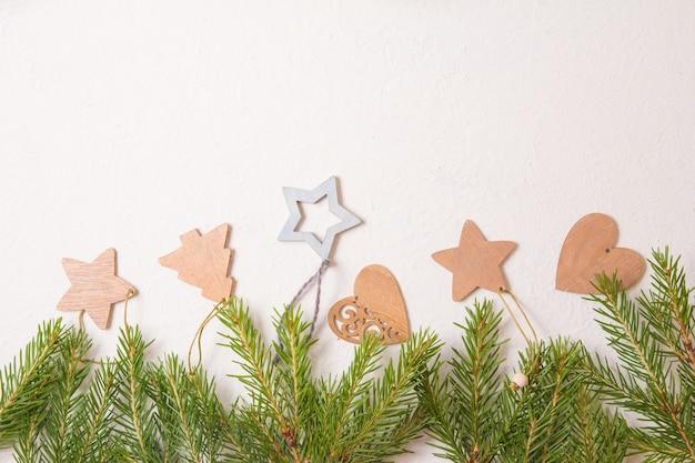 Weihnachtsbaumspielzeug und tannenzweige auf einem weißen hintergrund-draufsicht-kopierplatz, rahmen aus frischen natürlichen tannenzweigen und umweltfreundlichem weihnachtsbaumschmuck
